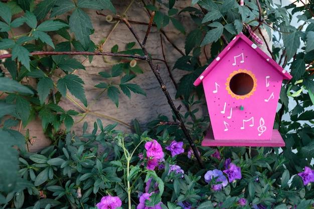 Ein rosa vogelhäuschen hängt an einem baum, der von petunienblumen umgeben ist.