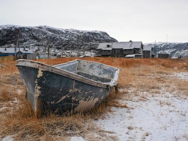 Ein rostiges gefrorenes fischerboot. altes fischerdorf am ufer der barentssee, der kola-halbinsel