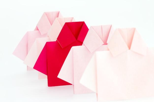 Ein rot unter weißem origami shirt papier, einzigartige individualität und differenz oder leadershi