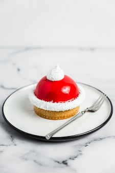 Ein rot-weißes mousse-tartelett-dessert auf einem weißen teller, eine dessertgabel