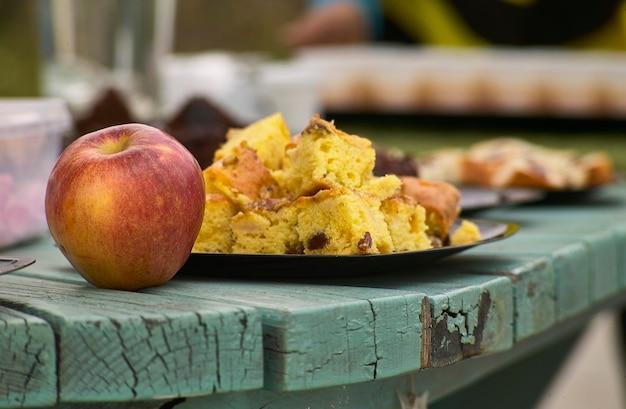 Ein roter apfel und ein teller mit einer scheibe süßes: ein gesunder und natürlicher snack, der typisch für die nördlichen regionen italiens ist. biologisches und natürliches süßes essen.
