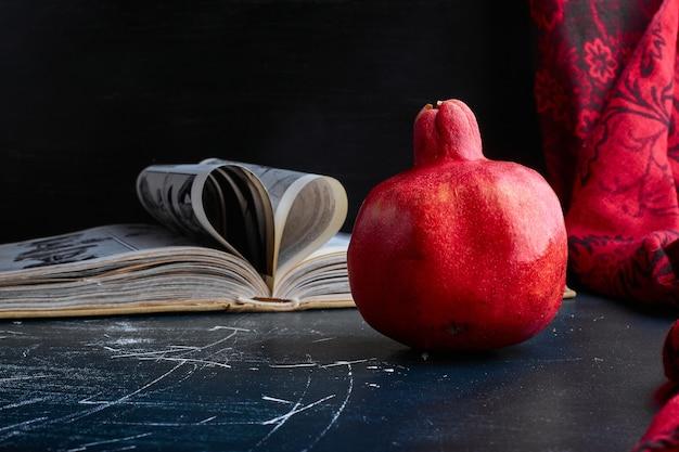 Ein roter einzelner granatapfel auf schwarzem hintergrund.