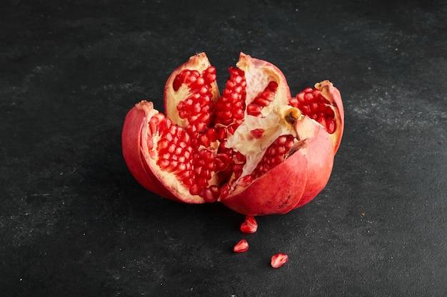 Ein roter granatapfel in stücke gerissen.
