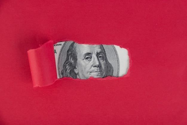 Ein roter hintergrund, unter dem ein porträt eines fünfzig-dollar-scheines guckt. genehmigtes darlehenskonzept