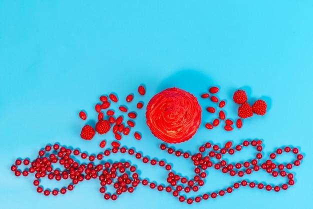 Ein roter kuchen der draufsicht mit roten bonbons breitete sich alles auf blauem schreibtisch aus, keksfarbene bonbons