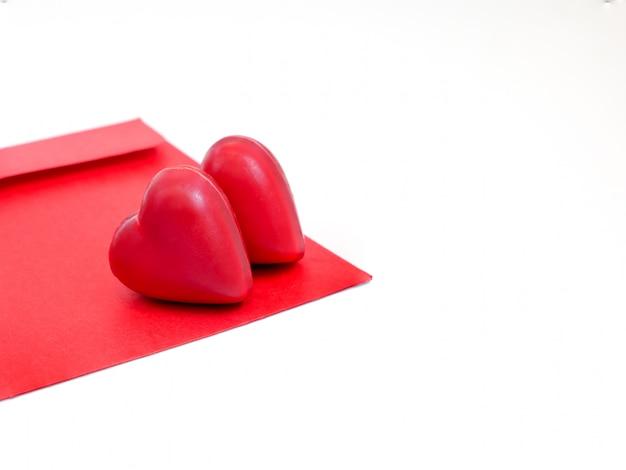 Ein roter liebesbriefumschlag mit zwei herzförmigen pralinen