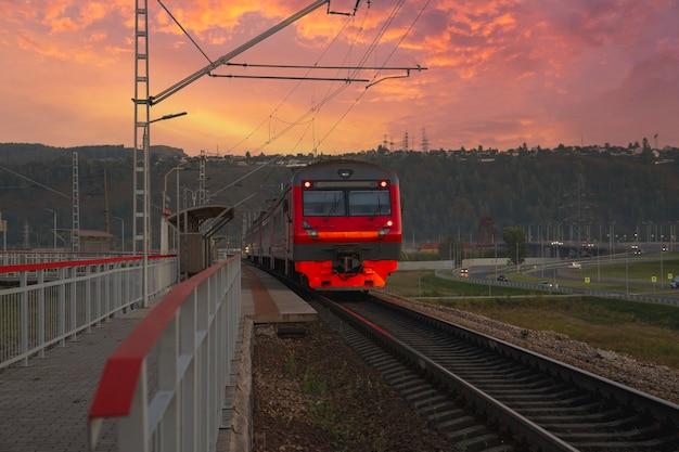 Ein roter personenzug kommt am bahnhof an. intercity-kommunikation.