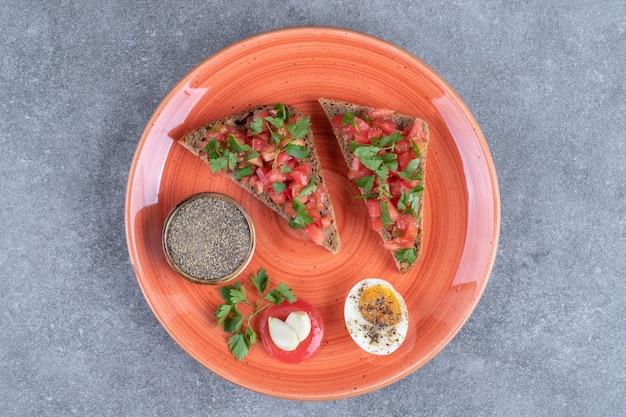 Ein roter teller mit gekochtem ei und toast. hochwertiges foto