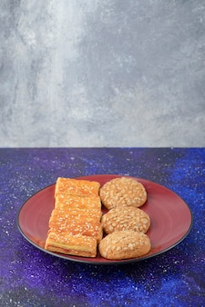 Ein roter teller mit gesunden keksen und leckeren crackern auf dem galaxientisch.