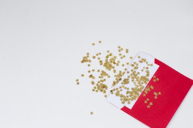 Ein roter umschlag und goldene sterne fliegen davon