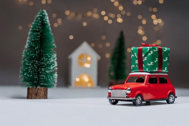 Ein rotes auto auf dem hintergrund eines waldes und eines hauses bringt weihnachtsgeschenke des neuen jahres.