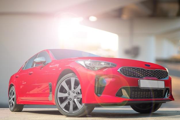 Ein rotes auto auf einem hintergrund der stadtumgebung.