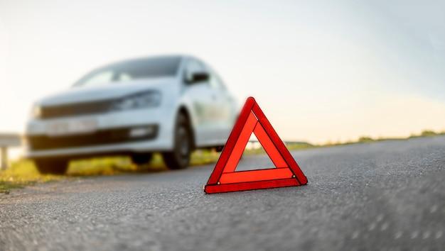 Ein rotes dreieckszeichen auf der straße als symbol des autounfallunfalls auf der autobahn
