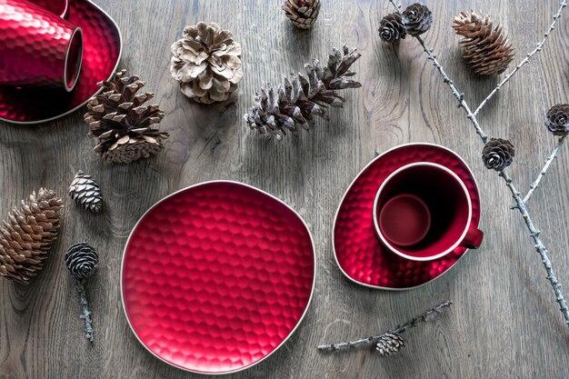 Ein rotes geschirr: eine teetasse, eine untertasse, ein teller und verschiedene zapfen auf einem hölzernen hintergrund. weihnachtstischdekoration, magische feiertage.