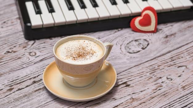 Ein rotes herz auf den schlüsseln und eine tasse zimtkaffee auf dem holztisch. unterbrechen sie die arbeit an der musikverarbeitung.