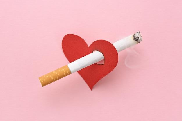 Ein rotes herz, aufgespießt von einer brennenden zigarette, dem schaden des rauchens, der die gesundheit zerstört.