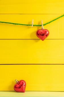 Ein rotes herz, das am grünen seil ein anderer roter herztropfen auf dem boden auf gelbem hölzernem brett hängt.