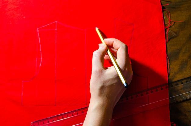 Ein rotes kleid machen. schneiderkleider. markieren von kleidern aus dem fertigen produkt. zeichnung eines roten kleides. kreieren sie ein babyrotes kleid