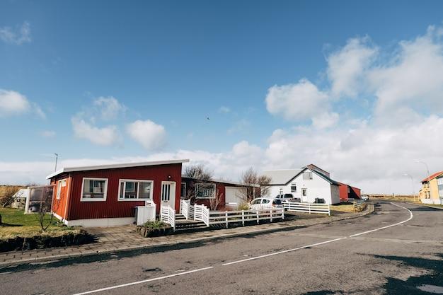 Ein rotes mehrfamilienhaus mit weißen fenstern und einem zaun an der straße eines wohngebiets