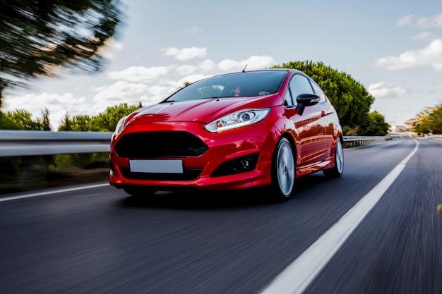 Ein rotes mini-coupé, das auf der autobahn mit hoher geschwindigkeit fährt.