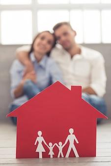 Ein rotes papierhaus und ein schönes paar.