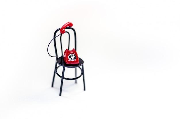 Ein rotes retro-telefon auf schwarzem stuhl