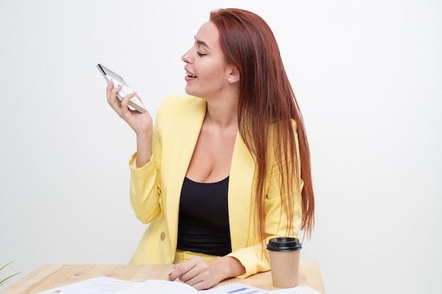 Ein rothaariges mädchen in einem gelben business-anzug sitzt an einem tisch und spricht auf einem taschenrechner wie am telefon. müdigkeit bei der arbeit