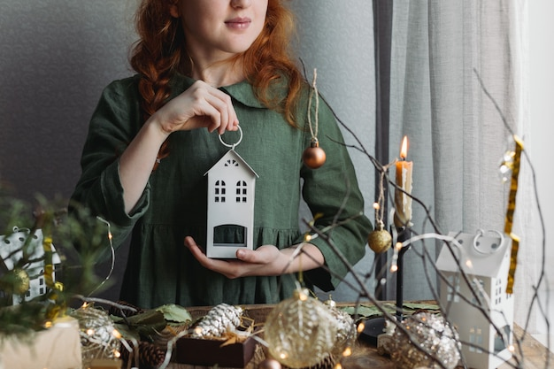 Ein rothaariges mädchen in einem grünen leinenkleid betrachtet weihnachtsdekorationen.