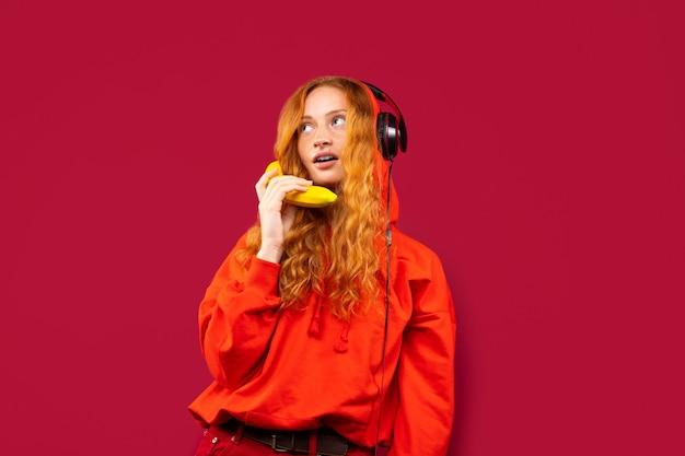 Ein rothaariges mädchen in einem roten hemd und großen kopfhörern hört musik und posiert mit einer banane. foto auf einer roten wand, das konzept der erholung und des zeitvertreibs.