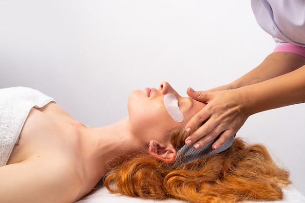 Ein rothaariges mädchen mit in ein handtuch gewickelten flecken macht eine gesichtsmassage in einer kosmetikklinik. gesundes hautkonzept. foto auf weißer wand.
