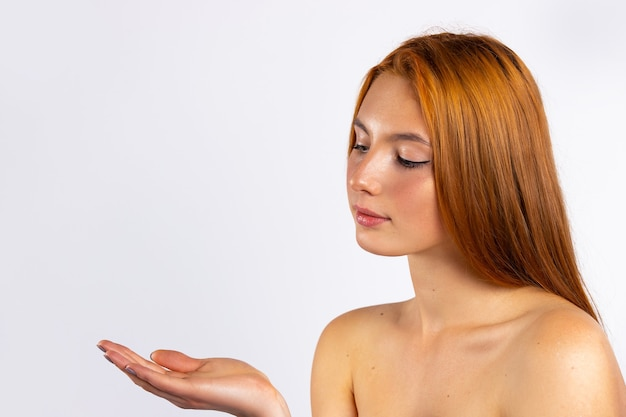 Ein rothaariges mädchen mit sommersprossen und langen haaren schaut sanft auf ihren teich. gesundes hautkonzept. foto mit leerem raum. hochwertiges foto