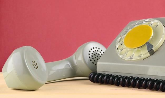Ein rotierendes retro-telefon auf einem schreibtisch gegen rote wand