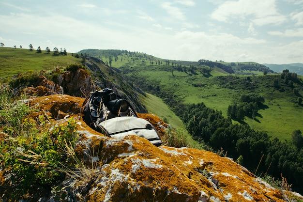 Ein rucksack mit fotoausrüstung ruht auf einem felsen mit blick auf die berglandschaft.