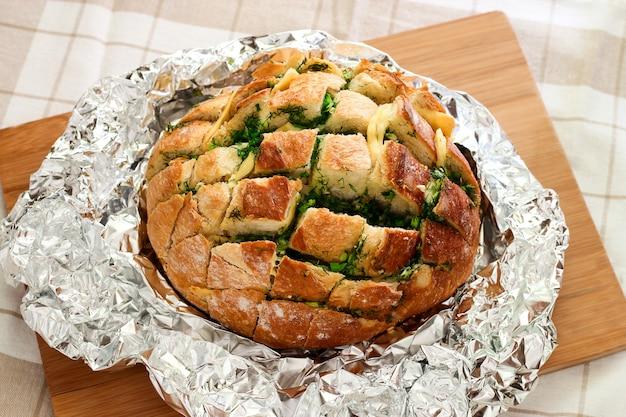 Ein runder laib duftendes brot, gefüllt mit geschmolzenem käse, kräutern und knoblauch, in folie gebacken. auf einem hölzernen, hellen hintergrund. draufsicht