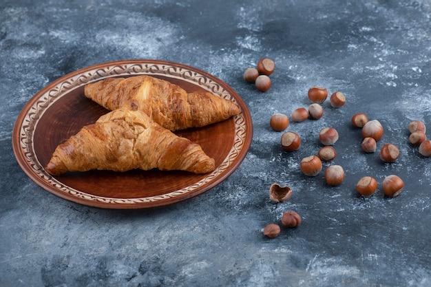 Ein runder teller mit frischen croissants und gesunden macadamianüssen.