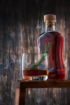 Ein rundes glas mit einem schuss whisky und einem rosmarinzweig