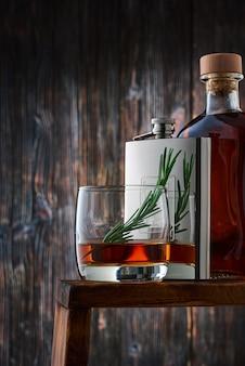 Ein rundes glas mit einer portion whisky und einem rosmarinzweig