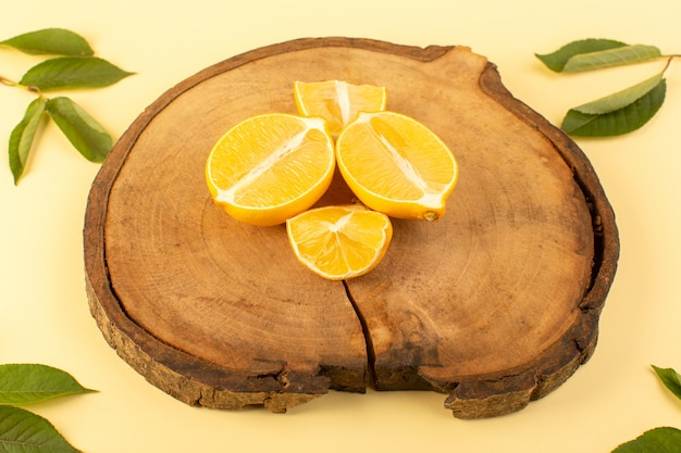 Ein rustikaler brauner holzschreibtisch der draufsicht zusammen mit grünen blättern und geschnittenen zitronen aprikosenfarben