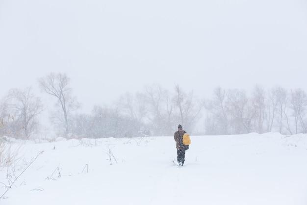 Ein rustikaler mann geht im winter mit einem gelben rucksack die straße entlang. schneesturm.