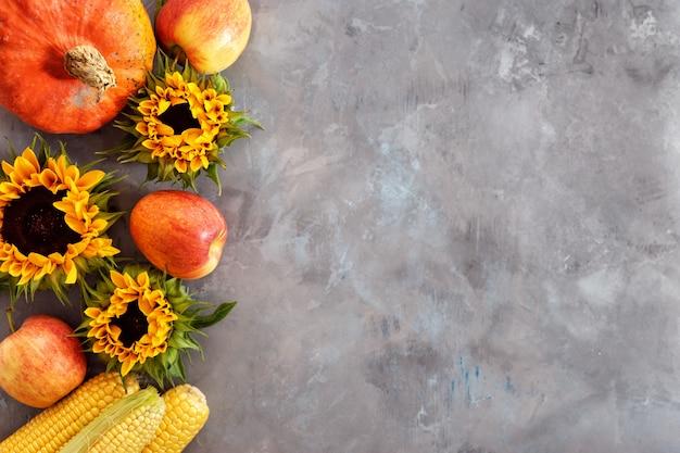 Ein rustikales herbststillleben mit kürbis, äpfeln und maiskolben