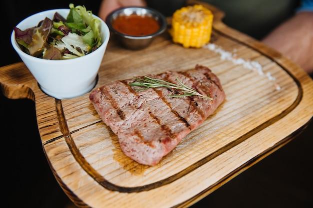 Ein saftiges steak aus gegrilltem fleisch mit salat, mais und soße
