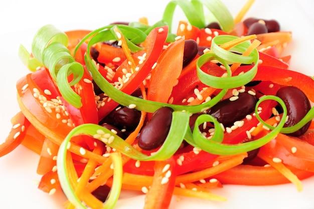Ein salat aus tomaten, paprika, roten bohnen, karotten mit sesam