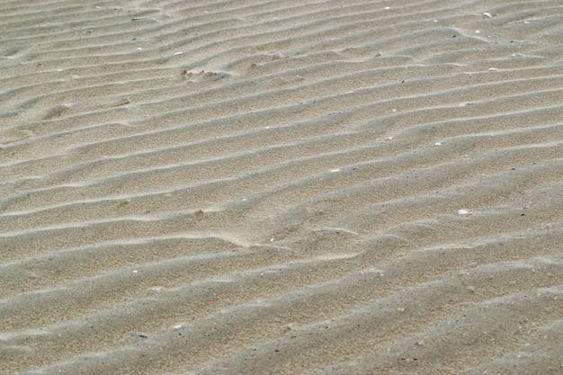 Ein sandiges muster gemacht durch einen seewind auf dem strand. beschaffenheitshintergrund.