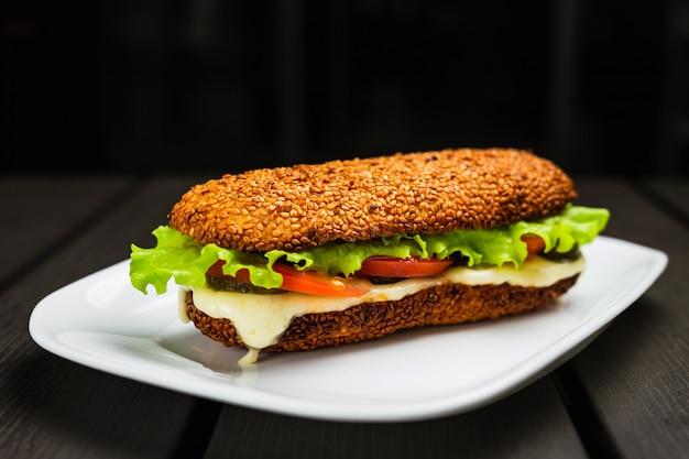 Ein sandwich mit heißem mozzarella, tomate, salat und gurken auf einem sesambrötchen