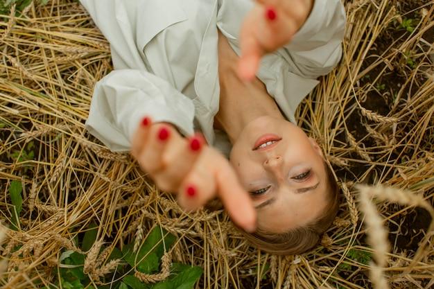 Ein sanftes mädchen liegt auf einem weizenfeld und streckt die hände nach der kamera aus.