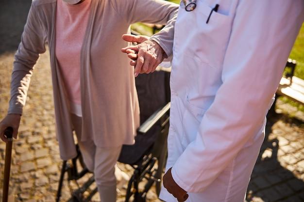 Ein sanitäter und eine ältere dame, die mit ihren händen zusammen in der nähe eines rollstuhls stehen standing