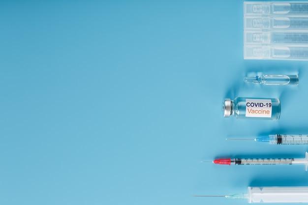 Ein satz ampullen mit der aufschrift covid-19-impfstoff und ein satz spritzen gegen