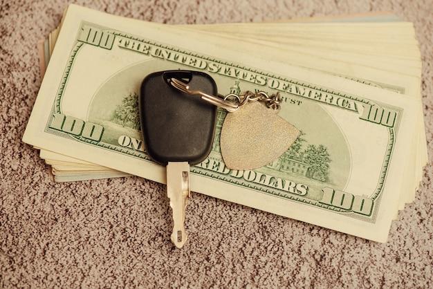 Ein satz autoschlüssel mit bargeld, autozahlung. autoschlüssel und dollar. schlüssel aus dem auto und geld