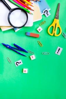 Ein satz bleistifte, notizbücher, kompassse, scheren isrepok auf grün