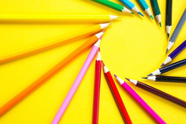 Ein satz bunter stifte auf gelbem grund ist in einem kreis in form der sonne angeordnet.